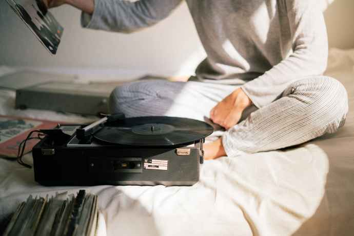 https://www.pexels.com/photo/person-in-gray-sweater-holding-black-vinyl-record-player-3618362/